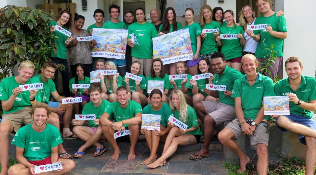 "Projects Abroad volunteers take a group photo with their ""I love sharks"" sign"